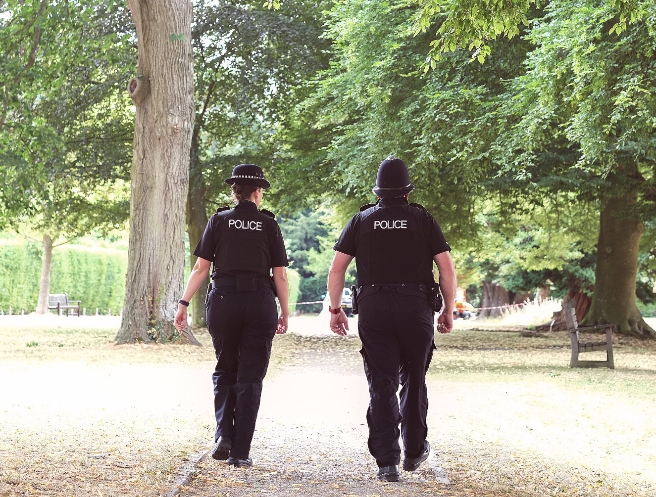 Police officers walking through a park
